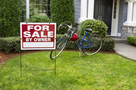 picture of yard sale  - Closeup view of Modern Suburban Home with for Sale Real Estate Sign in front yard and bicycle and house in background - JPG