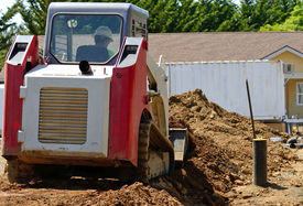 image of skid-steer  - Infrastructure excavation building contractors smoothing dirt over water lines in a utility trench at a commercial residential development - JPG