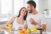 image of bonding  - Beautiful young couple bonding to each other and smiling while sitting in the kitchen together and having breakfast - JPG