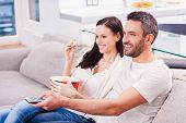 stock photo of bonding  - Beautiful young loving couple bonding to each other and eating popcorn while sitting on the couch and watching TV - JPG