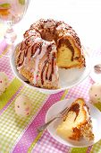 stock photo of sprinkling  - ring cake poured icing and chocolate sauce decorated with colorful sprinkles on easter table - JPG