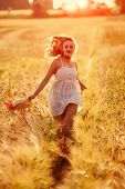 foto of golden  - Happy young blonde Scottish girl in white dress with straw hat running through the golden wheat field on sunset light behind her - JPG