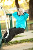 foto of 70-year-old  - 70 years old Senior Woman doing Exercises for Legs Outdoors in the Bright Autumn Evening - JPG