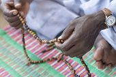 stock photo of rosary  - Hands of a Muslim man praying with rosary beads - JPG