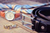 Постер, плакат: Leather belt tie cufflinks and watches on the old wood background Toned image