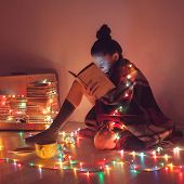 stock photo of cold-weather  - girl reading a book under blanket at home in cold weather