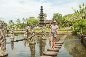stock photo of fountain grass  - Happy tourist at Tirtagangga water palace with fountains  and ponds on Bali - JPG
