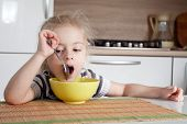 foto of cook eating  - Little girl is thinking about something while eating - JPG