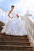 pic of fancy-dress  - Beautiful bride wearing a fancy wedding dress on the stairs looking at camera in the sunny day - JPG