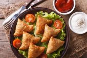 stock photo of samosa  - samosa on a plate with sauce and tomatoes closeup - JPG