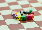 stock photo of bff  - chess board brown white squares letters BFF bracelet best friend cubes balls - JPG