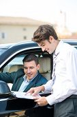 foto of rental agreement  - Car dealer and happy smiling man signing a contract. Concept for car rental ** Note: Soft Focus at 100%, best at smaller sizes - JPG