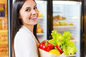 stock photo of refrigerator  - Beautiful young woman holding shopping bag with fruits and smiling while standing in grocery store near refrigerator - JPG