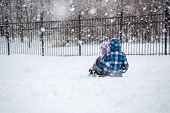 stock photo of sled  - Children Sledding in Winter Snowfall Outdoors on a Snowy Day - JPG