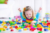 stock photo of brick block  - Cute funny preschooler little girl in a colorful shirt playing with construction toy blocks building a tower in a sunny kindergarten room - JPG