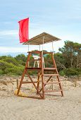 stock photo of lifeguard  - Empty lifeguard tower with red flag on the beach - JPG