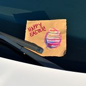 Постер, плакат: Happy Easter Message under a windshield wiper