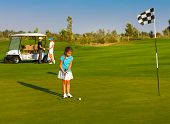 stock photo of sportive  - Young sportive family playing golf on a golf course - JPG