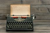 pic of typewriter  - antique typewriter with grungy textured paper page on wooden table - JPG