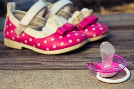 pic of pacifier  - Baby shoes and a pacifier on the old wooden background. Toned image