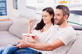 picture of bonding  - Beautiful young loving couple bonding to each other and eating popcorn while sitting on the couch and watching TV - JPG
