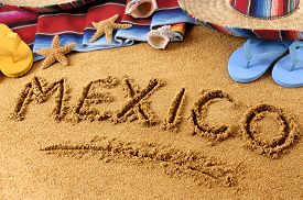 stock photo of starfish  - The word Mexico written in sand on a Mexican beach with sombrero straw hat traditional serape blanket starfish and seashells - JPG