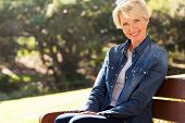 image of beautiful senior woman  - attractive senior woman sitting on a bench outdoors - JPG