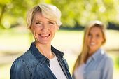 picture of close-up middle-aged woman  - portrait of middle aged woman in front of young daughter outdoors - JPG