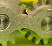 picture of kinetic  - Metal shiny cogwheel element shot on green paper background as closeup image - JPG
