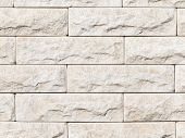 picture of cleaving  - wall of rough natural light beige marble stone with the cleaved surface laid horizontally like a brick - JPG