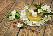pic of jasmine  - A cup of jasmine tea with jasmine flowers on a wooden background - JPG