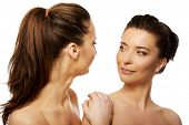 pic of topless  - Two attractive topless sisters with make up looking at each other - JPG