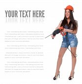 stock photo of hammer drill  - Young sexy female dressed in jeans and orange helmet holding hammer  electric drill - JPG