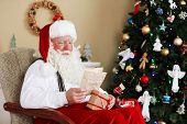 foto of letters to santa claus  - Santa Claus sitting with children letters in comfortable chair near fireplace at home - JPG
