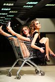 picture of trolley  - Two young enigmatic playful fashionable girls in dresses with shopping trolley indoor on store backdrop vertical picture - JPG