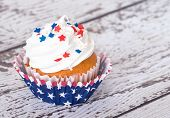 stock photo of sprinkling  - Cupcake with patriotic 4th of July sprinkles on vintage background - JPG
