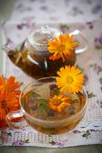 stock photo of marigold  - Herbal tea with marigold flowers on the table - JPG