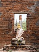 picture of buddha  - Sitting position buddha golden statue sitting on buddha statues without head arm and old Brick in Ayutthaya historical park Ayutthaya Thailand - JPG