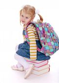 picture of knapsack  - little girl  blonde  with a school knapsack on his back  sitting on a stack of books - JPG