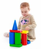 picture of montessori school  - Little girl playing in the cylinders and the cubes sitting on the floor - JPG