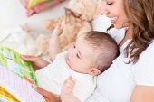 pic of reading book  - Joyful Mother Showing Images In A Book To Her Cute Little Son - JPG