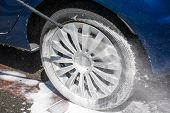 stock photo of pressure-wash  - Washing a dirty wheel with a high pressure jet wash - JPG