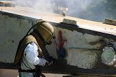 picture of sandblasting  - Worker is removing paint by air pressure sand blasting - JPG