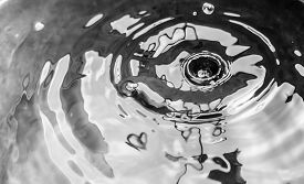 pic of leak  - Water drops from a leaking pipe causing ripples on water surface in black and white - JPG