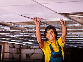 image of suspenders  - Man in builder uniform installing suspended ceiling - JPG