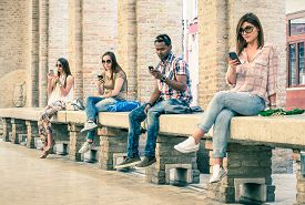 stock photo of addicted  - Group of young multiracial friends using smartphone with mutual disinterest towards each other  - JPG