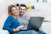 pic of internet shop  - Smiling young couple making shopping online with credit card and laptop at home - JPG