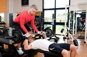 picture of work bench  - Young man doing weigths on a bench press with the help of the mature instructor at gym - JPG