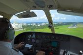 stock photo of san juan puerto rico  - Pilot is getting ready for landing overlooking the city ocean beach and landing strip on the background.