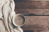 Cup of hot coffee on rustic wooden table, closeup photo warm sweater with mug, winter morning concep poster